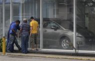 Men look at the price of Peugeot cars in Havana January 3, 2014. REUTERS/Enrique de la Osa