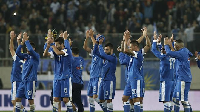 Greece's players celebrate their 3-1 win against Romania after the end of  a World Cup qualifying playoff first leg soccer match at the Karaiskaki stadium in the port of Piraeus, near Athens, Friday, Nov. 15, 2013