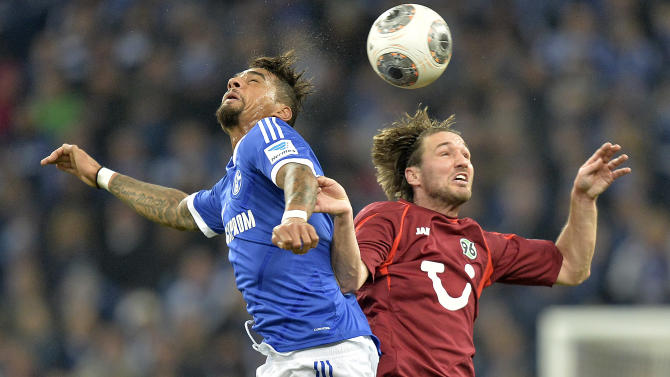 Schalke's Kevin-Prince Boateng, left, and Hannover's Christian Schulz challenge for the ball during the German Bundesliga soccer match between FC Schalke and SV Hannover in Gelsenkirchen,  Germany, Sunday, Feb. 9, 2014