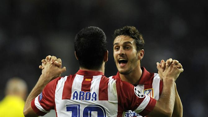 Atletico's Arda Turan celebrates with Koke, background, after scoring his side's second goal during the Champions League group G soccer match between FC Porto and Atletico de Madrid Tuesday, Oct. 1, 2013, at the Dragao stadium in Porto, northern Portugal. Atletico won 2-1