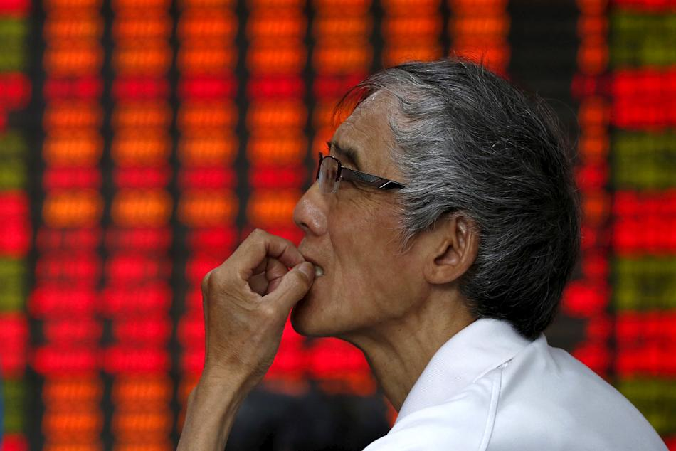 An investor looks at an electronic board showing stock information at a brokerage house in Shanghai
