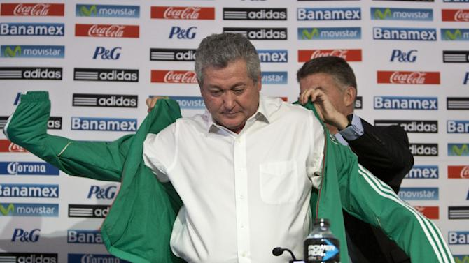 """Victor Manuel Vucetich puts on his new team's jacket with the help of Hector Gonzalez Inarritu, the director of Mexico's national soccer teams, as Vucetich is named the new coach for Mexico's national soccer team in Mexico City, Thursday, Sept. 12, 2013.  Vucetich is one of the most successful coaches in the local league, where hes known as """"King Midas"""" after winning 14 of 15 the finals he has managed in his career.  He replaces Jose Manuel De la Torre who was fired on Saturday after a loss to Honduras"""