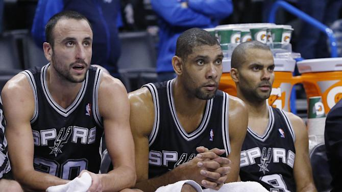 San Antonio Spurs guard Manu Ginobili (20), forward Tim Duncan (21) and guard Tony Parker (9) watch from the bench in the fourth quarter of an NBA basketball game against the Oklahoma City Thunder in Oklahoma City, Wednesday, Nov. 27, 2013. Oklahoma City won 94-88