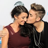Justin Bieber, right, kisses his mother Pattie Mallette as they arrive at the 40th Anniversary American Music Awards on Sunday, Nov. 18, 2012, in Los Angeles. (Photo by Jordan Strauss/Invision/AP)