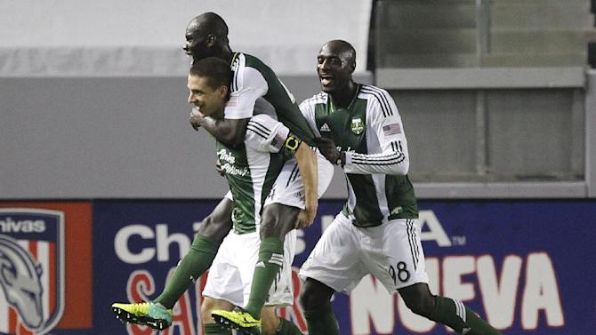Portland Timbers defender Pa-Modou Kah, center, leaps onto midfielder Will Johnson to celebrate Johnson scoring against Chivas USA with Timbers defender Mamadou Danso, right, during the second half of an MLS soccer match, Saturday, Oct. 26, 2013, in Carson, Calif. Timbers won the match 5-0