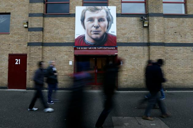 Supporters walk past new artwork of club legend Bobby Moore outside the ground, ahead of the English Premier League football match between West Ham United and Sunderland at The Boleyn Ground in Upton