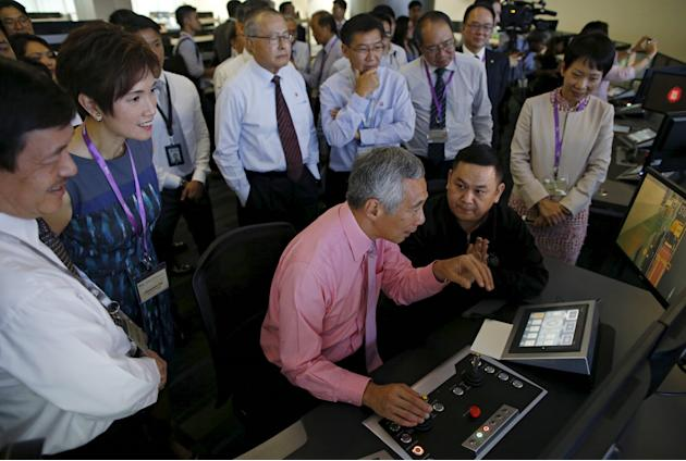Singapore's PM Lee is shown how to operate a crane after the opening of the PSA's Pasir Panjang Terminal Phases 3 and 4 in Singapore
