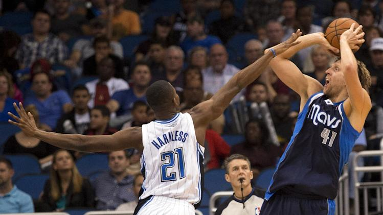Dallas Mavericks' Dirk Nowitzki, right, shoots a fade away jump shot against Orlando Magic's Maurice Harkless during the first half of an NBA basketball game in Orlando, Fla., Saturday, Nov. 16, 2013
