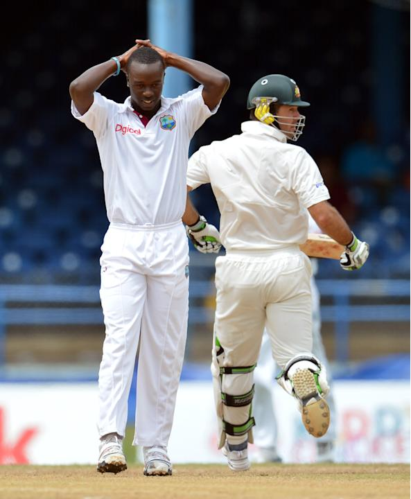 West Indies bowler Kemar Roach (L) react