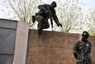 A Malian soldier leaps over a wall as another stands guard on April 3, 2012 at the Kati military camp near Bamako. The soldiers who staged a putsch in Mali five weeks ago say they have defeated an overnight counter-coup by foreign-backed forces loyal to ousted president Amadou Toumani Toure