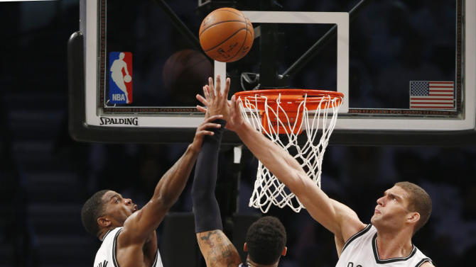 Brooklyn Nets forward Joe Johnson and Nets center Brook Lopez (11) block a shot by Atlanta Hawks forward Mike Scott (32) in the second quarter of Game 4 of a first round NBA playoff basketball game, Monday, April 27, 2015, in New York. (AP Photo/Kathy Willens)