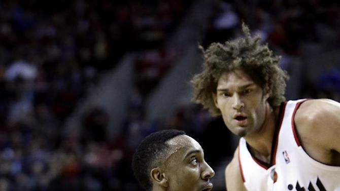 Atlanta Hawks guard Jeff Teague, left, drives to the basket as Portland Trail Blazers center Robin Lopez defends during the first half of an NBA basketball game in Portland, Ore., Wednesday, March 5, 2014. (AP Photo/Don Ryan)