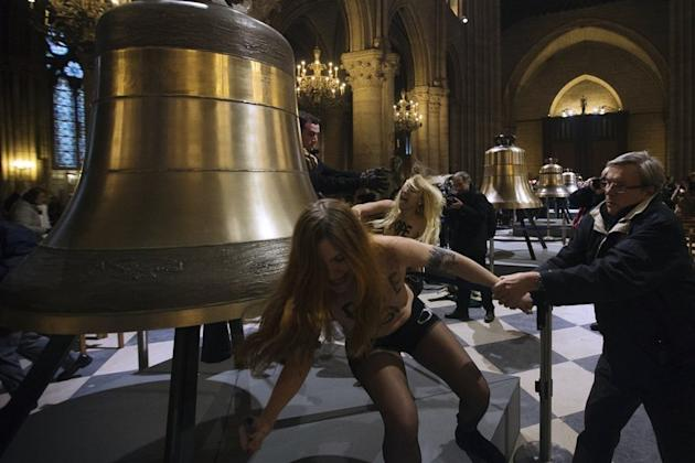 Activists from the Femen women's rights movement protest in front of the new eight bronze bells displayed in the nave of Notre Dame cathedral in Paris February 12, 2013. Eight feminists flashed their breasts in the heart of the cathedral on Tuesday to celebrate Pope Benedict XVI's shock resignation announcement