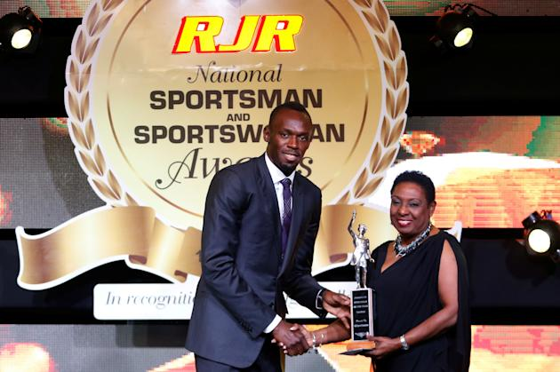 Jamaican sprinter Bolt is being presented with the Sportsman of the Year 2016 award by Minister of Information, Youth, Sports and Culture Grange in Kingston