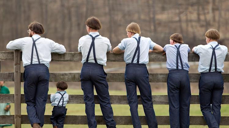 Amish boys watch a game of baseball outside the school house in Bergholz, Ohio, on Tuesday, April 9, 2013.  Many Amish families gathered following the final day of school for a celebration and farewell picnic. (AP Photo/Scott R. Galvin)