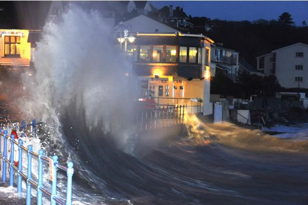 A large wave crashes over promenade at high tide in Saundersfoot in west Wales