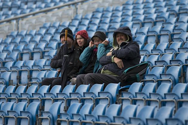Members of the public sit in near empty stands as rain falls before play on the first day of the second Test match between England and New Zealand at Headingley cricket ground in Leeds, England, Frida
