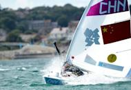 Xu Lijia of China waves as she celebrates her gold medal in the women's Laser Radial sailing class race at the London 2012 Olympic Games, in Weymouth