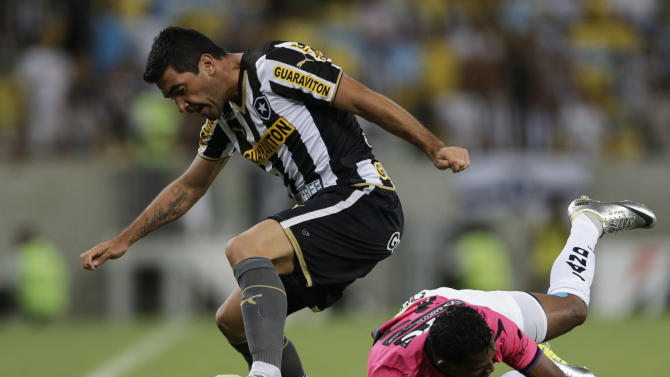 Juan Carlos Ferreyra of Brazil's Botafogo, left, fights for the ball with Fernando Alexander Vasquez of Ecuador's Independiente del Valle during a Copa Libertadores soccer match in Rio de Janeiro, Brazil, Tuesday, March 18, 2014