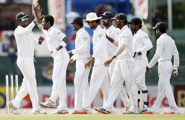 Sri Lanka's Prasad celebrates with captain Mathews and his teammates after taking the wicket of India's Pujara during the third day of their third and final test cricket match in Colombo