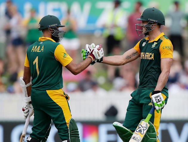 South Africa's Francois Du Plessis, right, is congratulated by teammate Hashim Amla after scoring a century during their Cricket World Cup Pool B match against Ireland in Canberra, Australia, Tues