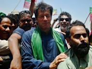 "Pakistani cricket legend turned politician Imran Khan is surrounded by his supporters during a campaign rally in Karachi on May 7, 2013. Khan, who won only one seat in 2002 and boycotted polls in 2008, has led an electric campaign, galvanising the middle class and young people in what he has called a ""tsunami"" of support that will propel him into office"