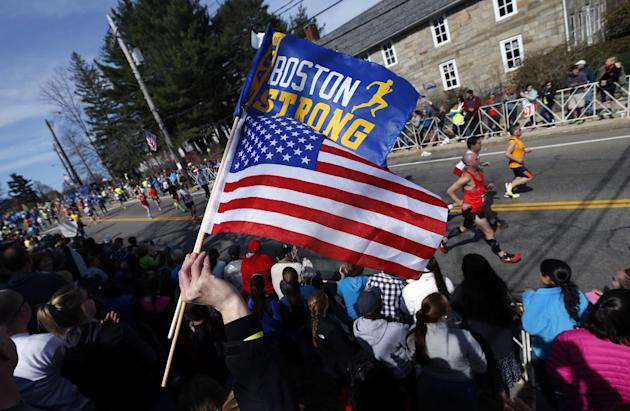 "A race fan waves the American flag and a banner bearing the slogan ""Boston Strong"" as runners compete in the 118th Boston Marathon Monday, April 21, 2014 in Hopkinton, Mass"