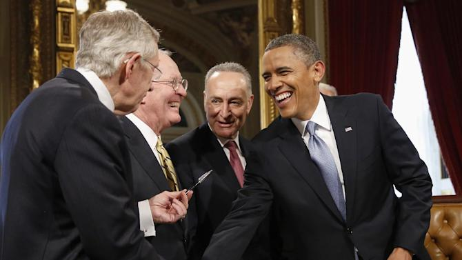 President Barack Obama laughs with, from left, Senate Majority Leader Harry Reid of Nev., Sen. Lamar Alexander, R-Tenn., and Sen. Charles Schumer, D-N.Y., on Capitol Hill in Washington, Monday, Jan. 21, 2013, after signing a proclamation to commemorate his inauguration, entitled a National Day of Hope and Resolve, following his ceremonial swearing-in ceremony during the 57th Presidential Inauguration.  (AP Photo/Jonathan Ernst, Pool)