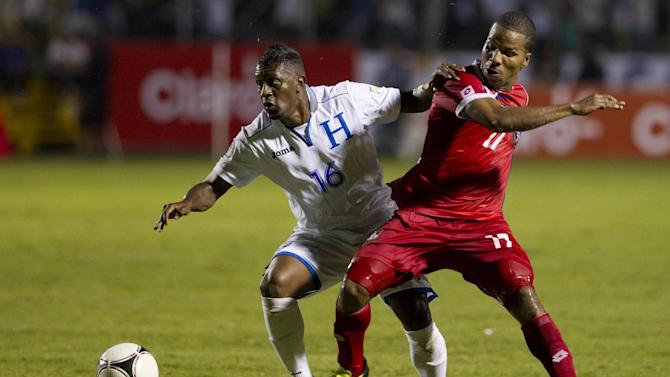 Honduras' Edgardo Alvarez, left, fights for the ball with Panama's Luis Henriquez at a 2014 World Cup qualifier soccer match in Tegucigalpa, Honduras, Tuesday, Sept. 10, 2013