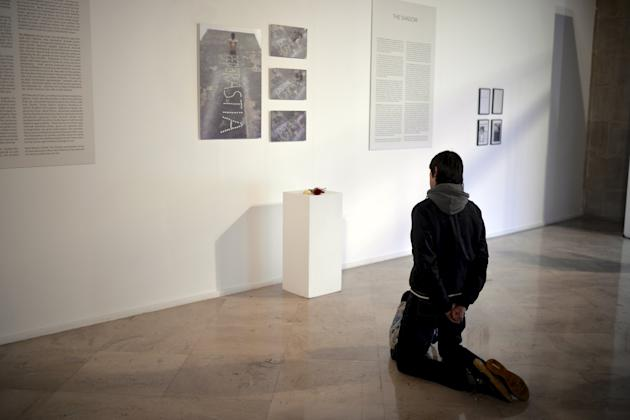 "Catholic protester kneels in front of photographs of consecrated hosts forming the word Pederastia (Paedophilia), at Spanish artist Abel Azcona's exhibition ""Desenterrados"" (Unearthed),"