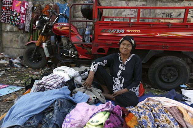 A woman selling clothes waits for customers near Duri train station in Jakarta
