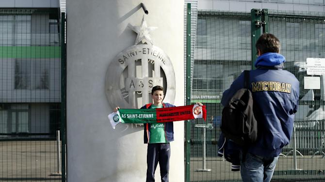 A fan poses for a picture outside the stadium before the match
