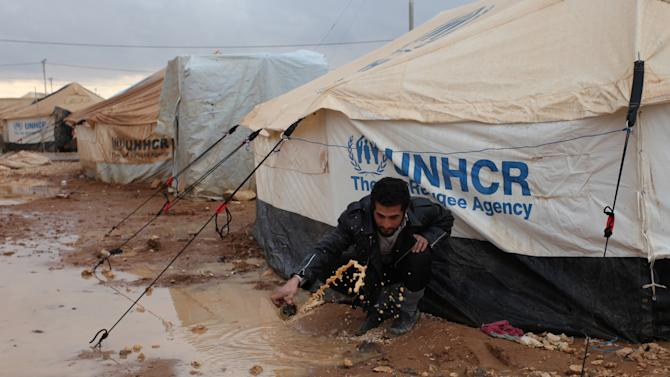 A Syrian refugee removes water and mud around his tent, at Zaatari Syrian refugee camp, near the Syrian border in Mafraq, Jordan, Tuesday, Jan. 8, 2013. Syrian refugees in a Jordanian camp attacked aid workers with sticks and stones on Tuesday, frustrated after cold, howling winds swept away their tents and torrential rains flooded muddy streets overnight. Police said seven aid workers were injured. (AP Photo/Mohammad Hannon)