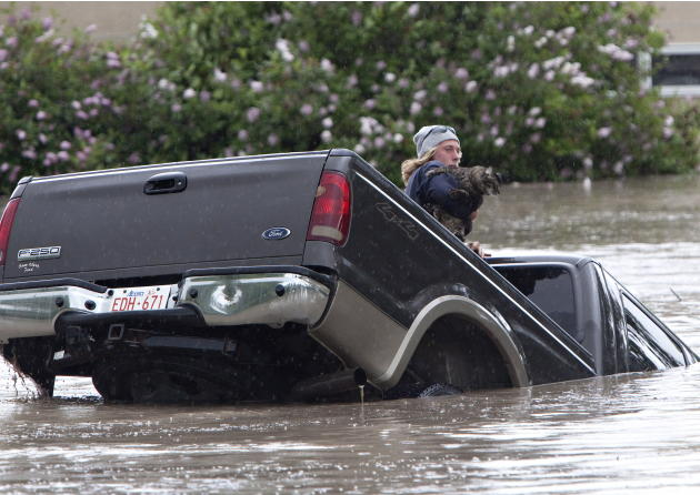Kevan Yaets crawls out the back window of his pick up truck with his cat Momo as flood waters sweep him downstream and submerge the cab in High River, Alberta on June 20, 2013 after the Highwood River