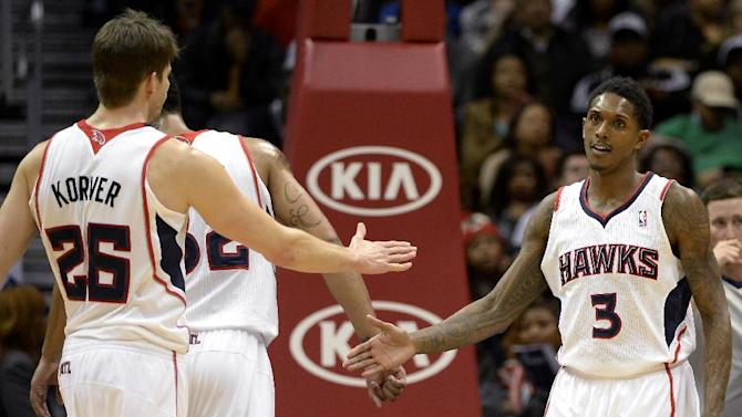 Atlanta Hawks' Lou Williams (3) is congratulated by teammate Kyle Korver (26) before he shoots free throws in the overtime period of their NBA basketball game on Saturday, Dec. 28, 2013, in Atlanta. Williams had 28 points in Atlanta's 118-116 overtime win