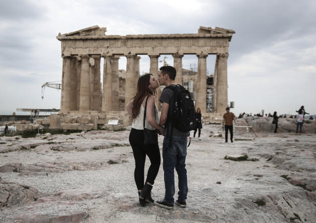 U.S. visitors Zach Branch,19, right, and Madison Franklin, 18, both from California, kiss in front of the Parthenon during their visit at the Acropolis hill in Athens, on Wednesday, April 15, 2015.  T