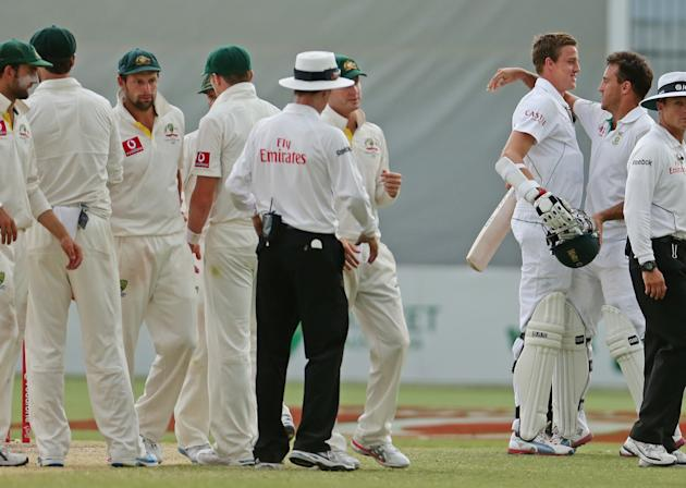 ADELAIDE, AUSTRALIA - NOVEMBER 26:  Michael Clarke of Australia looks on as Faf du Plessis and Morne Morkel of South Africa embrace at the conclusion of day five of the Second Test Match between Austr