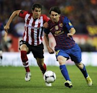 Athletic Bilbao's defender Borja Ekiza (L) clashes with Barcelona's forward Lionel Messi during the Spanish King's Cup final football match at the Vicente Calderon stadium, in Madrid. Barcelona won 3-0