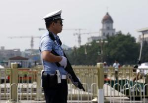 Policeman stands guard with a shotgun in front of Tiananmen …