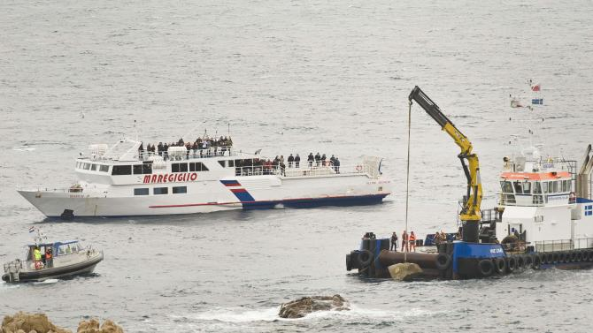 """Workers place part of the """"Le Scole"""" rock which was hit by the Costa Concordia cruise ship off the Tuscan Island Isola del Giglio, Italy, Sunday, Jan. 13, 2013. Survivors of the Costa Concordia shipwreck and relatives of the 32 people who died marked the first anniversary of the grounding Sunday. The first event of Sunday's daylong commemoration was the return to the sea of part of the massive rock that tore into the hull of the 112,000-ton ocean liner on Jan. 13, 2012 and remained embedded as the vessel capsized along with its 4,200 passengers and crew. (AP Photo/Antonello Nusca)"""
