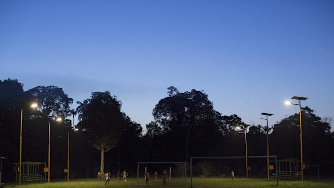 Residents play soccer at a field lighted with solar-powered lights at Vila Nova do Amana community in the Sustainable Development Reserve, in Amazonas state