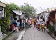 In this photo taken Aug. 3, 2011 in Manila, Philippines, a group of children practice their dance number in the alley on their village named after Marie Rose Abad who died during the Sept. 11, 2001 World Trade Center terrorist attacks in New York City. Unlike many victims of the 2001 attacks who are remembered mostly by their family and friends, Marie Rose Abad's legacy lives on half-way around the world in a once-notorious Manila slum now turned into a tidy village that carries her name. (AP Photo/Pat Roque)