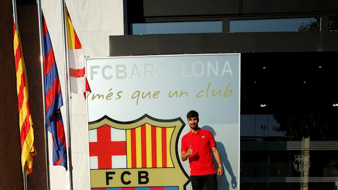 Soccer player Andre Gomes poses next to a FC Barcelona's giant logo at their offices in Barcelona