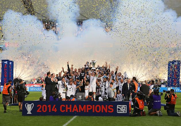 Players for the Los Angeles Galaxy hoist up the Philip F. Anschutz Trophy on the podium after defeating the New England Revolution in the 2014 MLS Cup on December 7, 2014 in Los Angeles, California