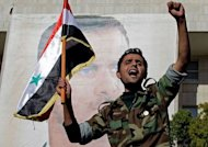 A Syrian soldier shouts slogans in front of a picture of President Bashar al-Assad during a pro-regime rally in Damascus on December 2. Syria said on Monday it conditionally accepts observers as part of an Arab plan, as a rights group reported militiamen loyal to the regime killed 34 civilians and dumped their bodies in a city square