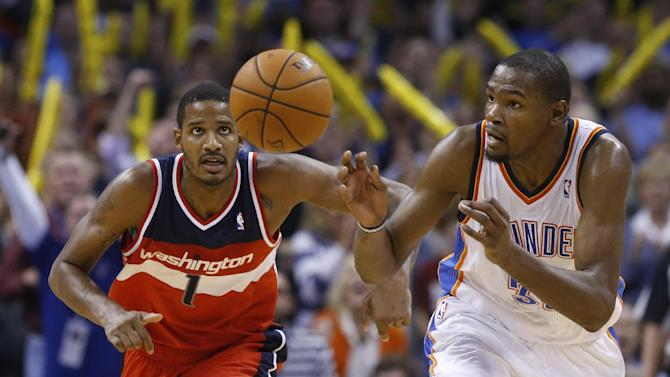 Washington Wizards forward Trevor Ariza (1)  and Oklahoma City Thunder forward Kevin Durant (35) chase a loose ball after Durant blocked a shot by Ariza in overtime  of an NBA basketball game in Oklahoma City, Sunday, Nov. 10, 2013. Oklahoma City won 106-105 in overtime