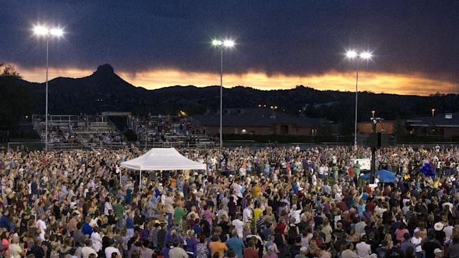 As the sun sets behind Granite Mountain, community members fill the football field at Prescott High School in Prescott, Ariz. to honor the 19 firefighters who died in the Yarnell Hill Fire. On Sunday, June 30, 2013, 19 members of the Granite Mountain Hotshots died in an out-of-control wildfire. (AP Photo/The Arizona Republic, Pat Shannahan)