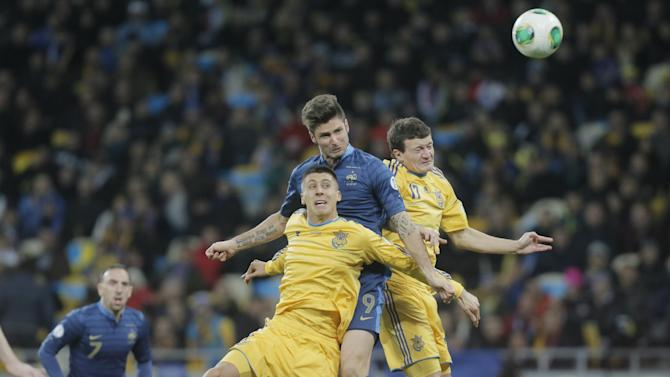 France's Olivier Giroud, center, in action with Ukraine's Yevhen Khacheridi, left, and Artem Fedetskiy during their 2014 World Cup qualifying soccer match at the Olympiyskiy national stadium in Kiev, Ukraine, Friday, Nov. 15, 2013