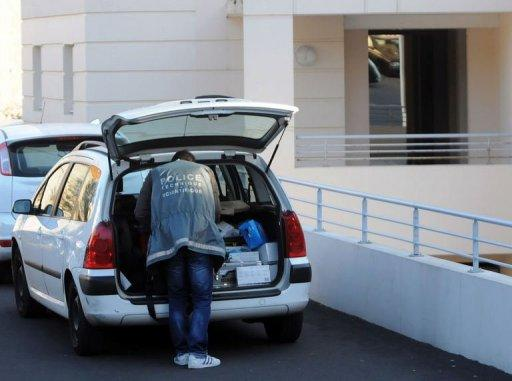 A forensic officer prepares his equipment outside a building in the southern French town of Sete, after a Frenchman enraged over a noisy birthday party went on a rampage killing two people.