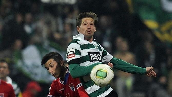 Sporting's Adrien Silva, right, vies for the ball with Gil Vicente's Luis Martins in a Portuguese League soccer match at the Cidade de Barcelos stadium, Barcelos, northern Portugal, Sunday, Dec. 8, 2013. Sporting won 2-0 and leads the championship ahead of rivals FC Porto and Benfica